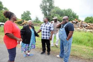 Residents talk as demolition goes on in the background. (Image from Southeast Missourian)